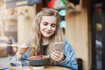 Lovely stylish female coworker in denim jacket and sunglasses gazing with romantic and cute smile at smartphone screen while eating soba with chopsticks in asian street cafe, messaging with boyfriend