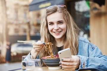 Stylish teenage girl cannot leave smartphone even while eating. Portrait of pleased and happy good-looking woman in trendy outfit and glasses, holding phone and chopsticks, eating asian food on street