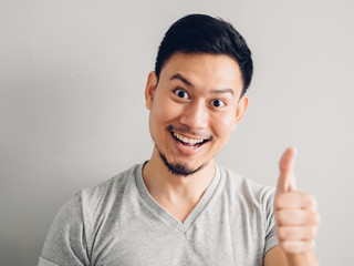 Headshot photo of Asian man with happy face. on grey background.