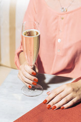 A glass of prosecco helds by a young woman in an elegant bar with vintage pop colors