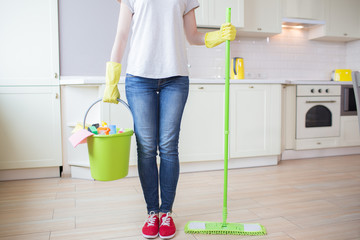 Cut view of woman stands in kitchen and holds stick with mop in one hand and bucket with cleaning equipment in the other one. Girl wears yellow gloves. Wall mural