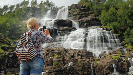 The tourist photographs the highest waterfall in Norway. According to legend, the water from this waterfall has a rejuvenating effect