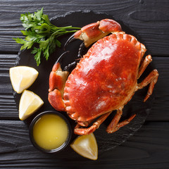 tasty boiled whole brown crab with sauce, lemon and parsley on a stone board close-up. top view