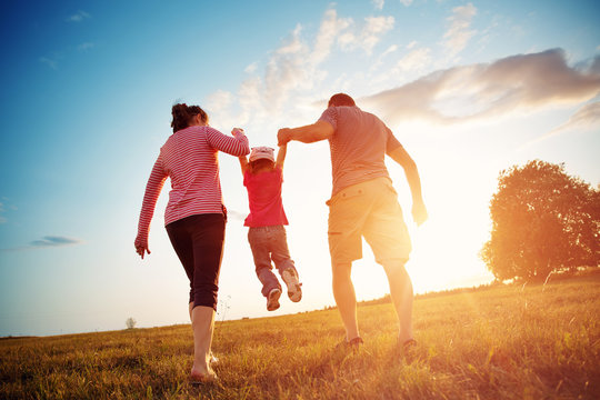 girl with mother and father holding hands on the nature. Child with parents outdoors