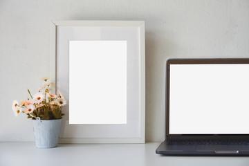 Mockup loft workspace, Blank screen laptop and mockup poster at white desk.