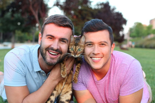 Gay couple in the park with their pet