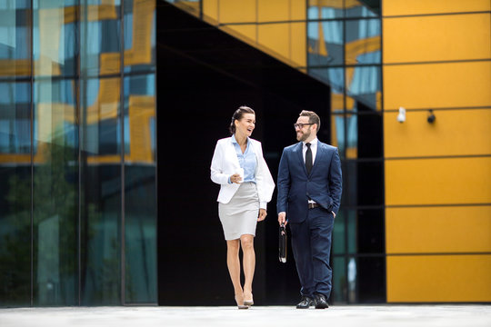 Young successful laughing male and female in business dress leaving office block, having dialogue