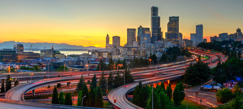 Panoramic view downtown Seattle skyscrapers and I-5 Freeway at I-90 interchange at orange sunset. Long exposure of traffic light trails during rush hour. View from Jose P. Rizal Bridge (12th bridge)