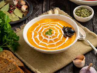 Funny food for Halloween. Pumpkin puree soup, spider web, dark old wooden table, side view.