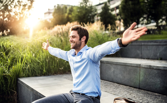 A happy young businessman with arms stretched outdoors at sunset.