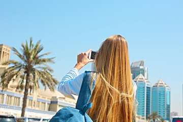 Woman taking mobile photo of the Central Souq in Sharjah City, United Arab Emirates