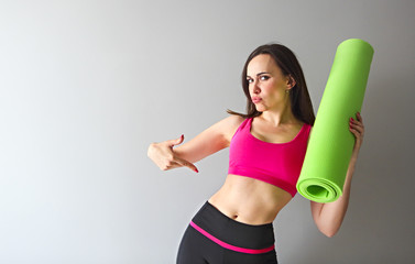 Attractive woman wearing pink sportswear holding green yoga or fitness mat after working out at home or in club.