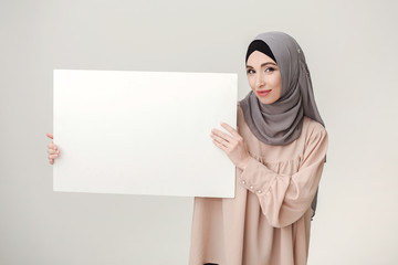 Muslim woman holding white banner for text or picture