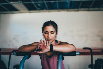 young woman having a look on smart watch while doing work out in gym