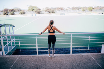 young atheltic woman looking at sports field