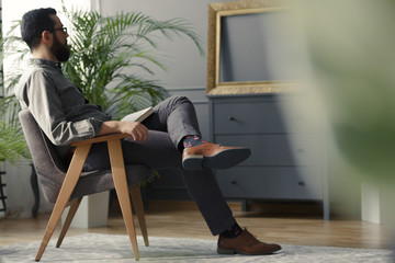 Low angle of hipster sitting on wooden armchair in grey vintage interior with plant