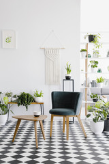 Real photo of plants, green chair and wooden coffee table in spacious, natural living room interior