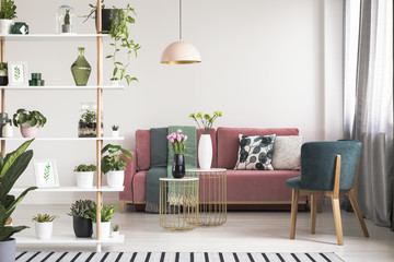 Real photo of a green armchair, pink couch, gold tables with flowers and wooden rack with plants in botanic living room interior Wall mural