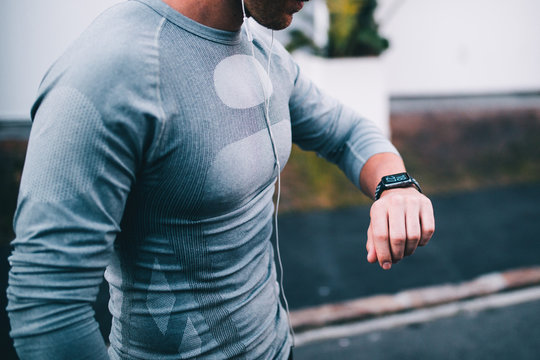 athletic man looking at smart watch while doing outdoor fitness