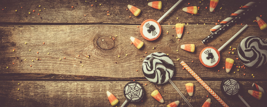 Halloween background - candies and lollipops, straws, wood background