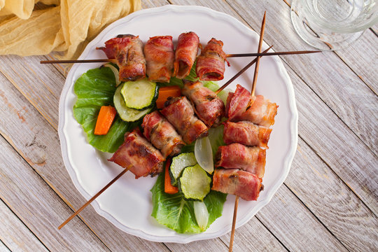 Chicken liver wrapped with bacon on skewers. Grilled liver kebabs with vegetables. View from above, top studio shot