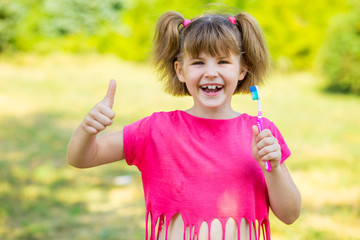 Happy little girl brushing her teeth with thumbs up. Dental hygiene. Healthy concept