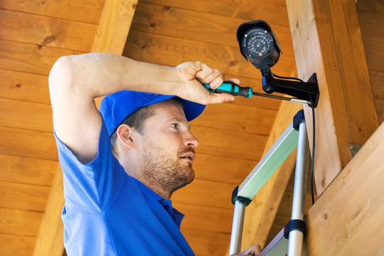 technician installing surveillance camera in the house carport