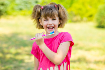 Happy little girl brushing her teeth. Dental hygiene. Healthy concept