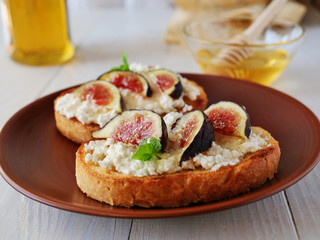 Bruschetta toast topped with goat cheese, fig slices, honey and herbs over wooden table