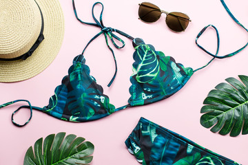 Tropical bikini swimsuit, beach fashion. Traveler woman accessories flat lay with swimwear, palm leaves.