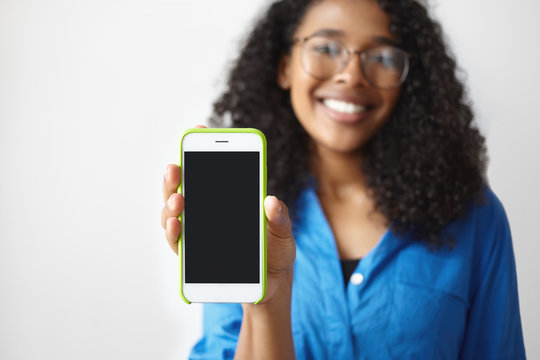 Picture of positive smiling young African American female in glasses holding generic mobile phone, showing blank display with copy space for your text or advertising content. Selective focus