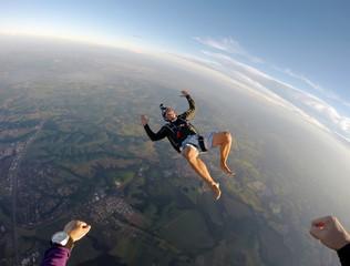 Barefoot man jumping from parachute at sunset.