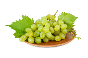White bunch of ripe grapes with leaves on brown ceramic plate isolated on white background. Berries of grapes in a bunch.
