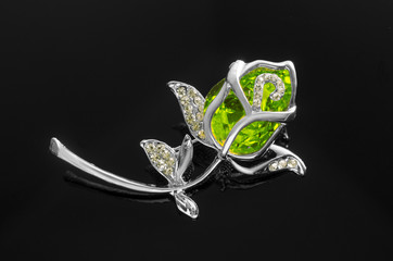 Wall Mural - silver brooch rose flower with green stone isolated on black