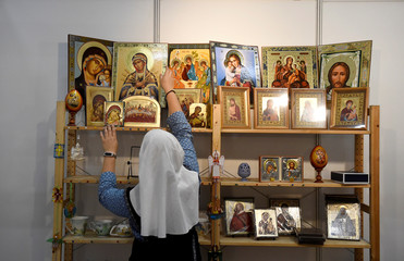 A Nun arranges religious pictures at a stall during the Papal Congress at the World Meeting of Families in Dublin, Ireland