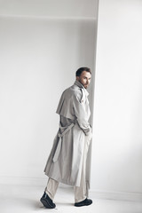 Fashion portrait of handsome man with dark beard and hair, weared in light trench coat, beige pants and black shoes. Man stands near white wall and looks back