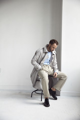 Fashion portrait of handsome  stylish man with dark beard and hair, weared in light trench coat, shirt, beige pants and black shoes. Man sits on the chair near white wall