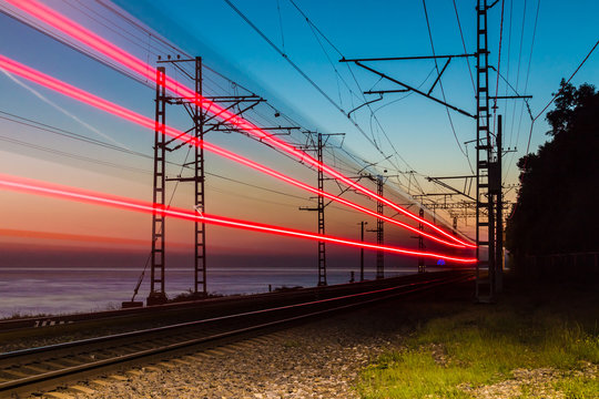 Beautiful landscape of a railroad with motion blurred train on the background of the sea at twilight, Sochi, Russia