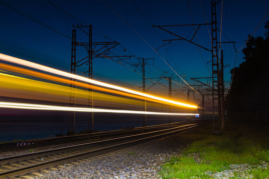 An illuminated railroad with light trails of a motion blurred train at dusk, Sochi, Russia