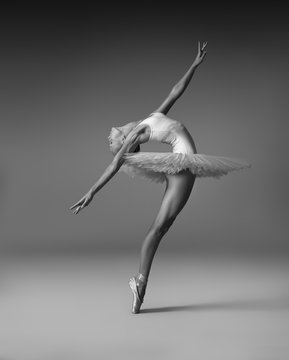 Ballerina in a tutu and pointe shoes makes a beautiful pose
