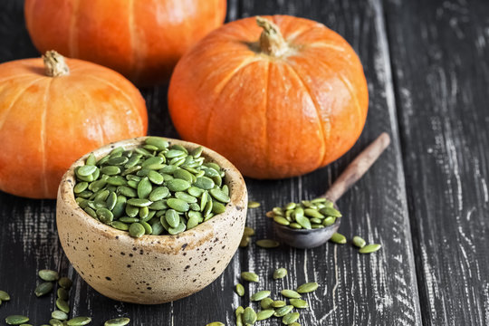 Bowl with pumpkin seeds and small pumpkin on a rustic table. Selective focus.
