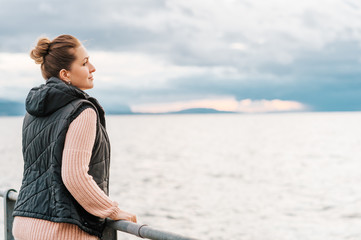 Outdoor portrait of young woman resting by the lake on a fresh cold day, wearing warm pullover