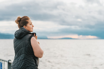 Outdoor portrait of young woman resting by the lake on a fresh cold day, wearing warm pullover and black down vest