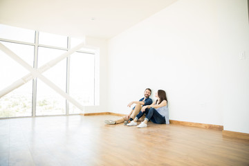 Man Talking With Woman In Empty Room Of New House