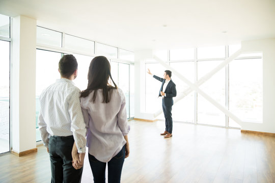 Couple Looking At Estate Agent Showing Window Of New Apartment