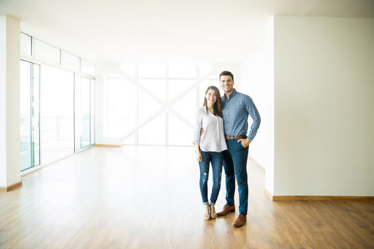 Happy Mid Adult Couple Standing In New Apartment