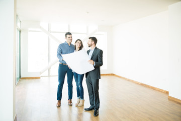 Couple And Estate Agent Discussing Over Blueprint In New Apartment