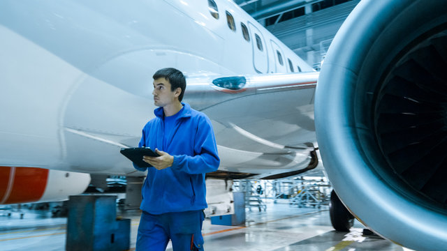 Aircraft maintenance mechanic uses tablet to inspect plane body in a hangar.