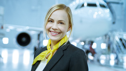 In a Aircraft Maintenance Hangar Young Beautiful Blonde Stewardess/ Flight Attendant Smiles Charmingly on Camera. In the Background Brand New Airplane is Visible.