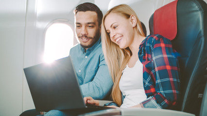 On a Board of Commercial Airplane Beautiful Young Blonde with Handsome Hispanic Male Watch Movies on a Laptop and Laugh. Sun Shines Through Aeroplane Window.